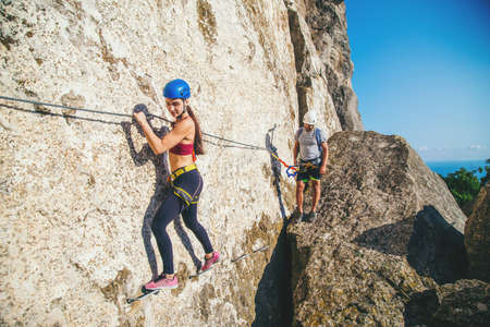 Woman and man  in helmet and special equipment climbing high mountain via ferrata. Crimea.