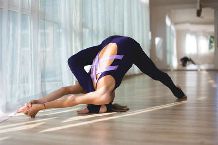 Woman makes yoga position standing widely in yoga studio. Yoga practice.