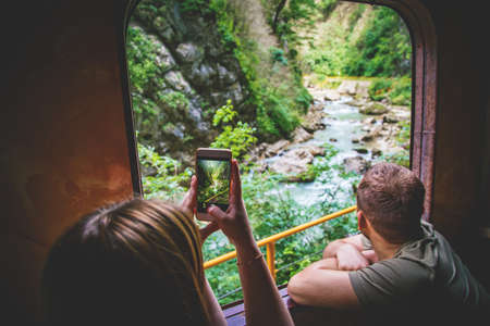 Young woman takes travel photo of canyon and river by her smart phone out of train window.