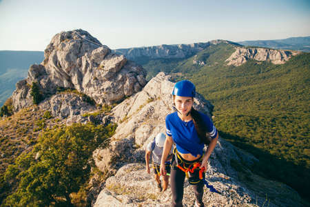 Couple of man and woman climbing mountain via ferrata in Crimea in helmets using safety device. Imagens