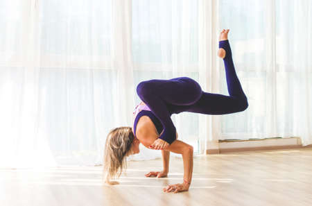 Woman makes yoga position standing on hands in yoga studio. Yoga practice. Imagens