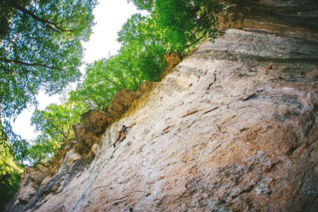 Athletic man climbing overhanging rock in the forest in Caucasus mountains. Imagens
