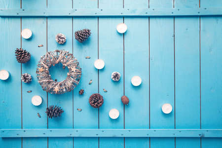 New Year and Christmas holiday decoration made of wreath, cones, candles, stars and lights on blue wooden background. Flat lay style.