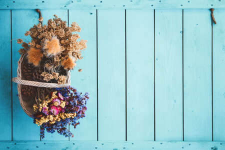 Autumn style basket full of dry flowers bouquets on blue colored wooden background.