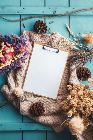 Blank paper, dry flowers and herbs, cones and seed composition autumn style on blue wooden background. Flat lay style. Imagens