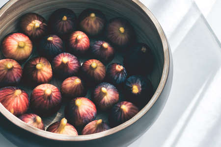 Cropped frame of  wooden plate full of ripe figs harvest on a table. Imagens