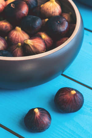 Cropped farme of wooden plate full of ripe figs harvest on a blue wooden table.