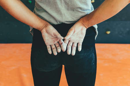 Woman hands covered with magnesia powder, back view. Waiting for bouldering training in gym. Imagens