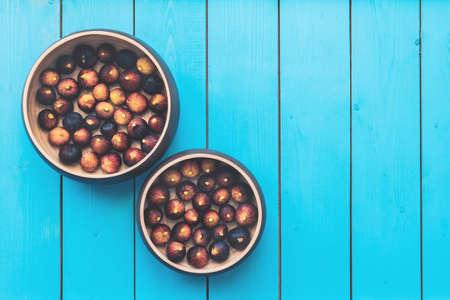 Dwa drewniane talerze pełne dojrzałych fig zbierają się na niebieskim drewnianym stole. Zdjęcie Seryjne