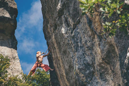 Athletic man climbs a crack rock in the forest with rope. Sport climbing in Crimea, lead.