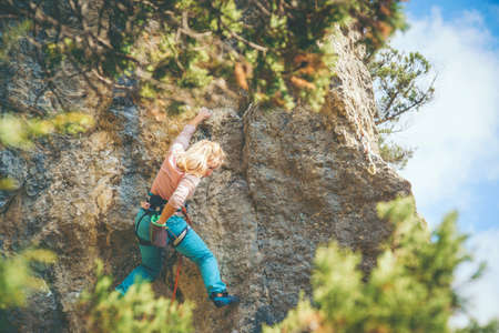 Beautiful blonde hair athletic girl climbing a rock with rope outdoor. Sport climbing.