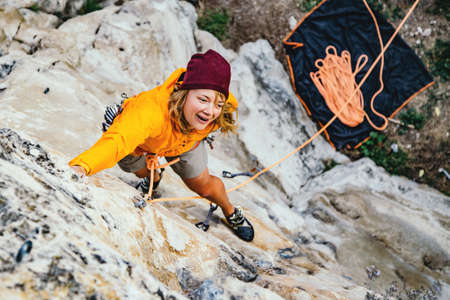 Young woman climbs an overhanging rock  with rope. Sport climbing, lead. Upper view.