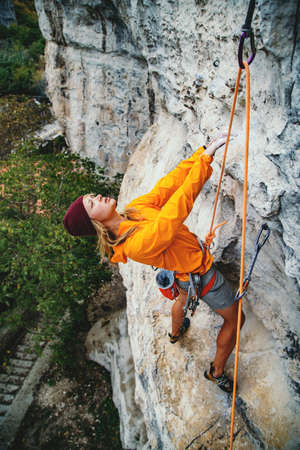 Young woman climbs an overhanging rock  with rope. Sport climbing, lead. Side view.
