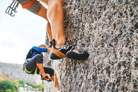 Cropped frame of female foot in climbing shoe standing on the rock hold. Side view, sport climbing. 版權商用圖片