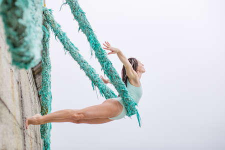 Woman makes yoga practice outdoor using blue rope like a hammock. Фото со стока