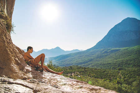 Men climber relaxing at the bottom of a rock on mountains background. Turkey Stock Photo
