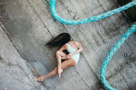 Woman makes yoga practice outdoor using blue rope like a hammopck. Stock Photo