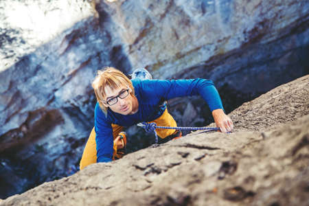Athletic man climbs very high tufa rock with rope in Turkey. Sport climbing, lead. Stock Photo