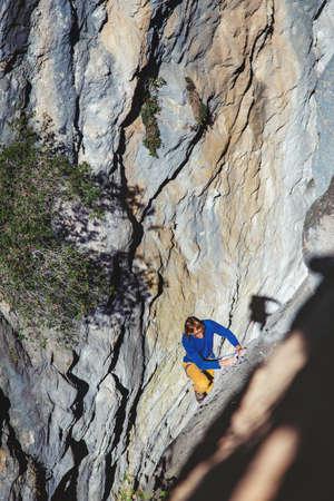Athletic man climbs very high tufa rock with rope in Turkey. Sport climbing, lead. 版權商用圖片