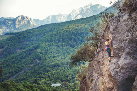 Young athletic woman climbs an overhanging rock with rope in Turkey. Sport climbing, lead. Upper view. Stock Photo