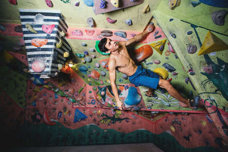 Young athletic man makes boulder training in small boulder gym. 版權商用圖片