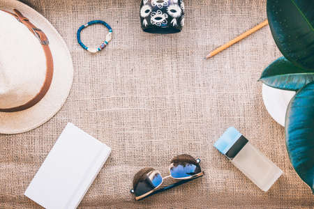 Composition of straw hat, female bracelets, white note pad, bottle of perfum, ficus hous palnt, pencil and sun glasses on brown jute background. Flat lay style for summer project.