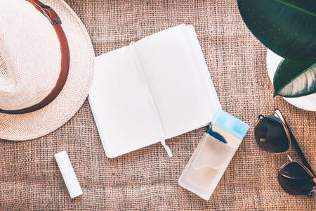Composition of straw hat, lip stick, white note pad, bottle of perfum, ficus hous palnt and sun glasses on brown jute background. Flat lay style for summer project.