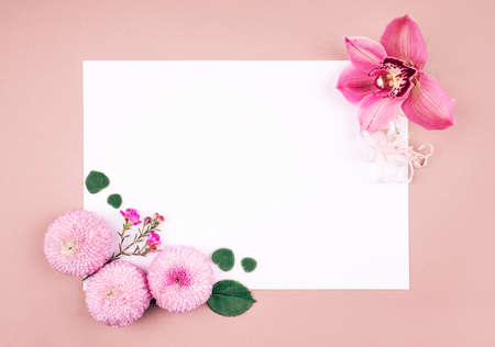Flower card made of orchid and chrisantemum flowers and baby eucalyptus leaves with white blank paper in the cennter. For holiday project.