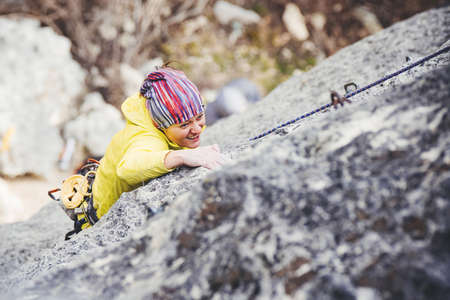 Athletic woman in colorful sportswear climbs a rock with rope. Sport climbing, lead. Top view. Crimea.