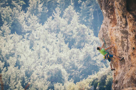 Athletic man climbs an overhanging rock with rope, lead climbing in Turkey. Sport climbing outdoor.