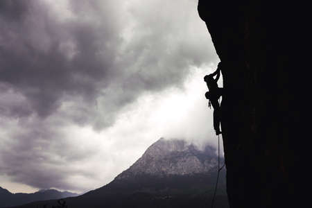 Silhouette of athletic man climbs an overhanging rock with rope, lead climbing in Turkey. Sport climbing outdoor.