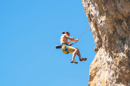 Athletic man climbs an overhanging rock with rope, lead climbing. Sport climbing outdoor. 版權商用圖片