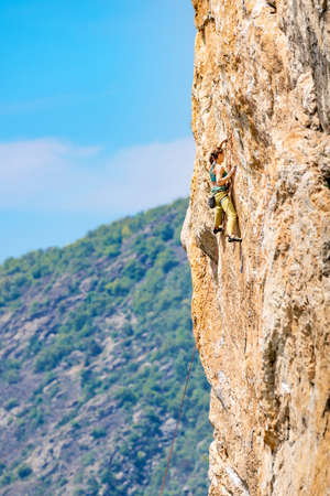 Athletic beautiful woman climbs an overhanging rock with rope, lead climbing. Sport climbing outdoor. 版權商用圖片