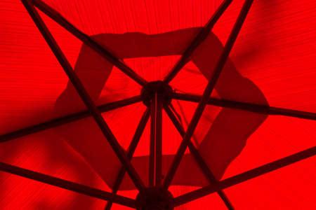 Underneath a red umbrella