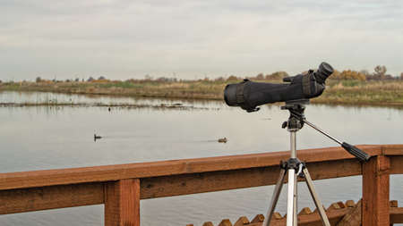 tripod mounted: A monocular mounted on a tripod is ready for birdwatching on a bordwalk Stock Photo