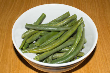 side order: Bowl of cooked green beans over wooden table