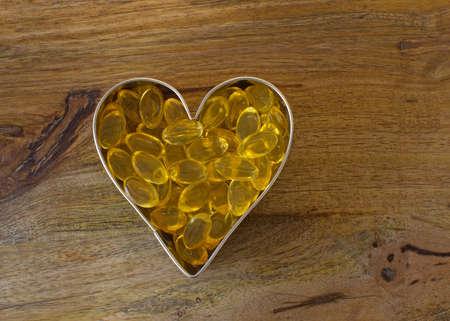 wood cutter: Garlic pills in metal heart over aged wood board