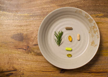 dietary supplements: A plate with dietary supplements over aged wooden board is ready to be consummed, Asian style Stock Photo