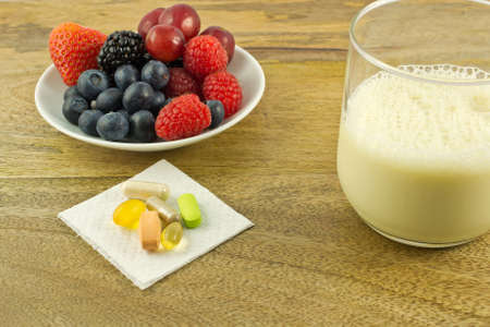 antioxidant: Berries, anti-oxidant supplements and a cup of soy milk on wooden table Stock Photo