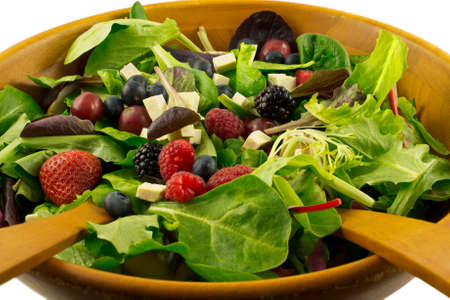 Organic mixed greens, berries and sprouted tofu salad served in wooden bowl, against white background