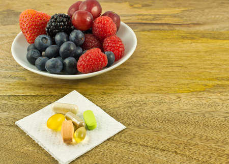 dietary supplements: Berries and dietary supplements on wooden table