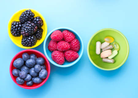 Berries and dietary supplements in colorful bowls viewed from above, on blue surface