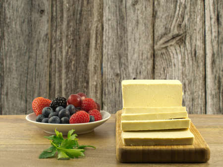 Antioxidant rich fruits and tofu on wooden table against wooden background