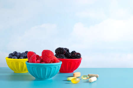 low carb diet: Blackberries, blueberries and raspberries in colorful bowls and an assortment of dietary supplements, on blue table against clouds background