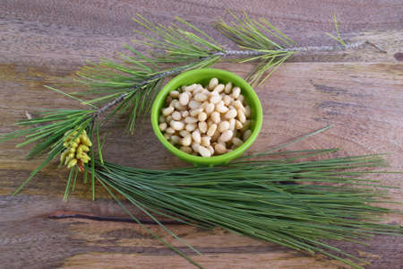 pinaceae: A bowl of pine nuts surrounded with pine needles on aged wooden table Stock Photo