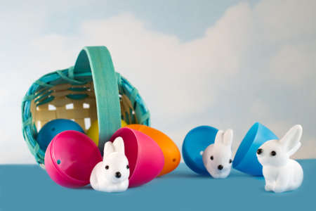 cuteness: Easter basket filled with plastic eggs rolls over and little white bunnies hatch from cracked eggs Stock Photo