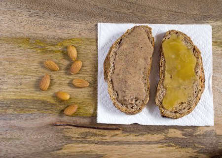 open topped: Rye bread topped with almond butter and raw crystallized honey for delicious healthy sandwitch on aged wooden board