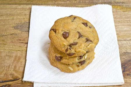 grasas saturadas: Tres chips de chocolate rallado almendras galletas apiladas sobre una toalla de papel, en la mesa de madera envejecida