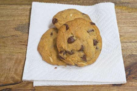 grasas saturadas: Tres galletas de chocolate con almendras trituradas apilados sobre una toalla de papel sobre la mesa de madera