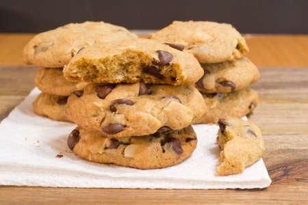 grasas saturadas: Nueve galletas de chocolate con almendras trituradas apilados sobre una toalla de papel sobre la mesa de madera Foto de archivo